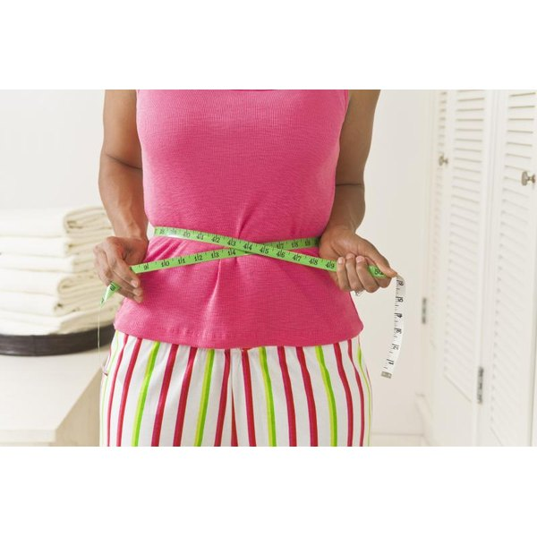 Woman using a tape measure on her waist.