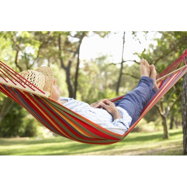 A man taking a nap in a hammock on a summer day.