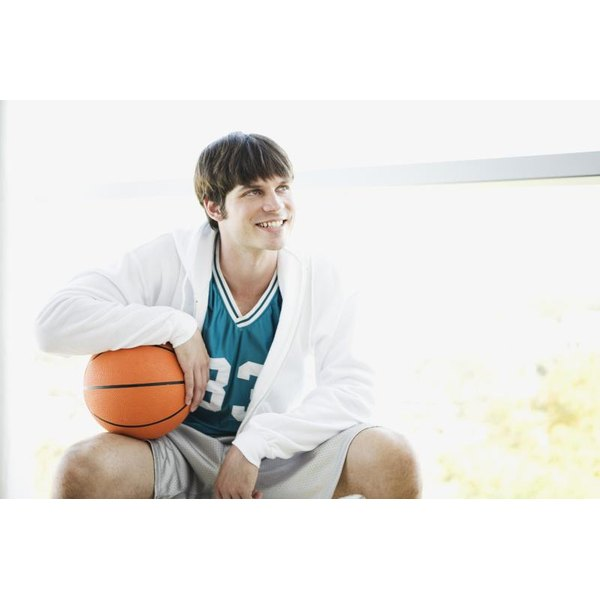 Basketball player sitting with ball.