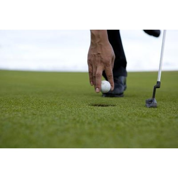A close-up of a golfer retrieving his ball from the hole.