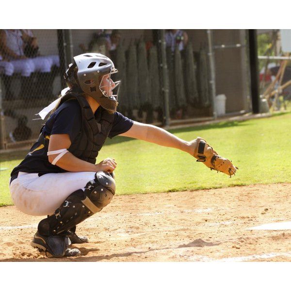 A catcher in position behind the plate during a softball game.