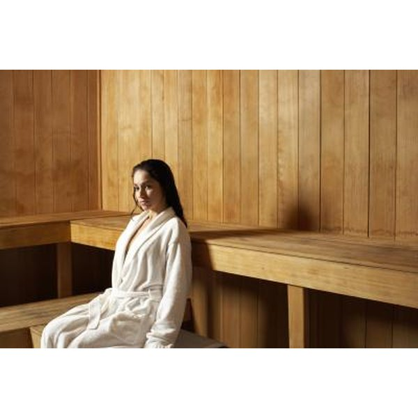 A woman in a robe sitting in a sauna.