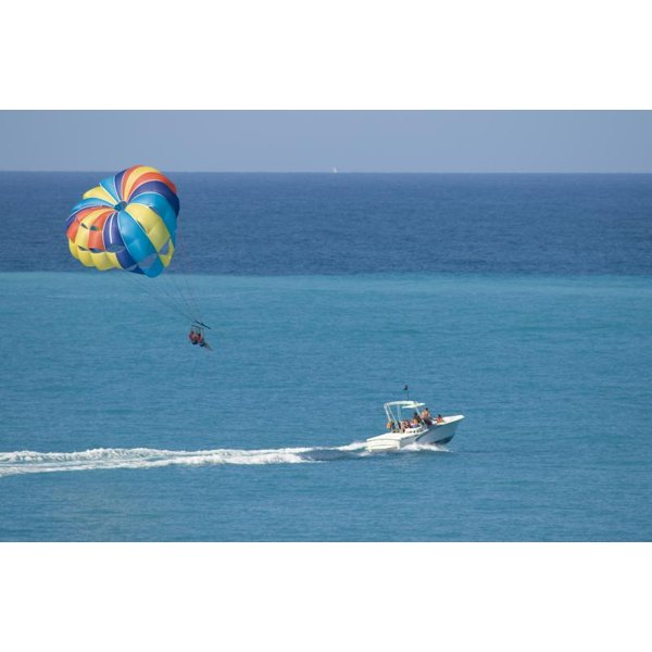Vacationer parasailing behind a boat in the tropics.