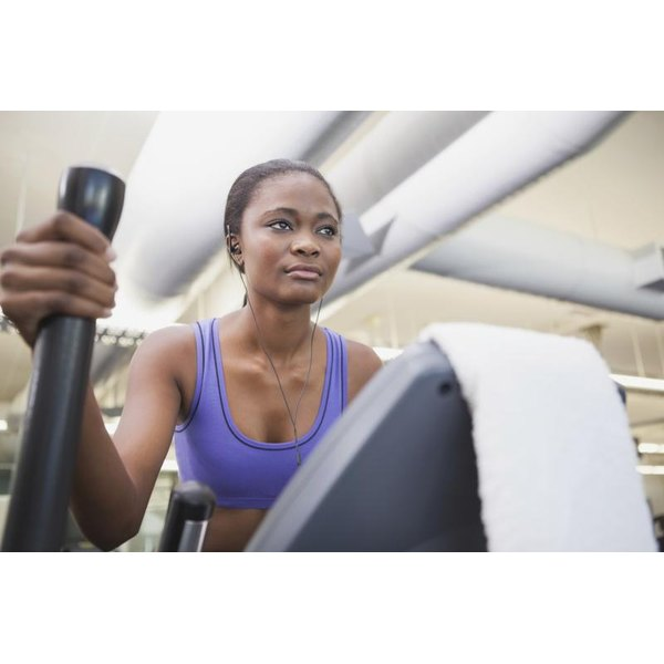 A woman is exercising on an elliptical machine.