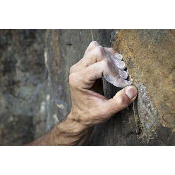 Close-up of a rock climber's hand gripping a ledge