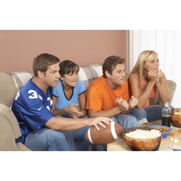 Group of friends watching football on television.