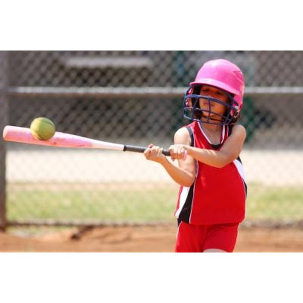Young girl swinging a bat and hitting a softball.