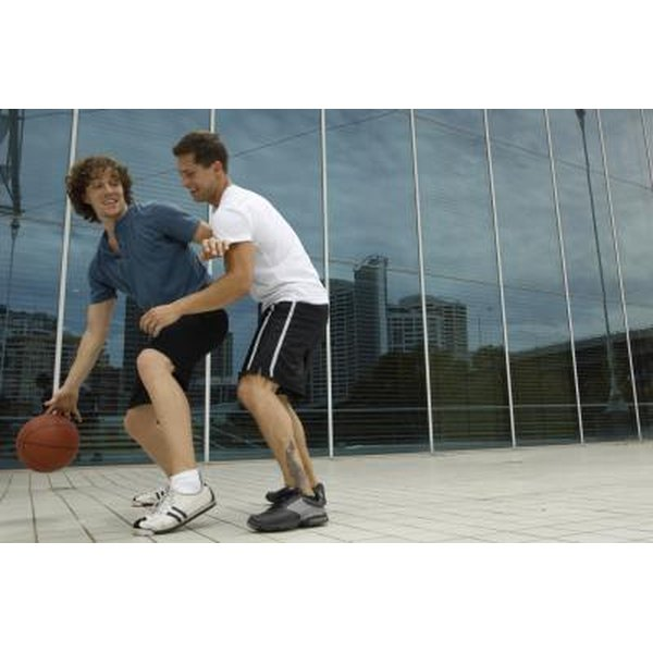 Two men playing basketball outside.