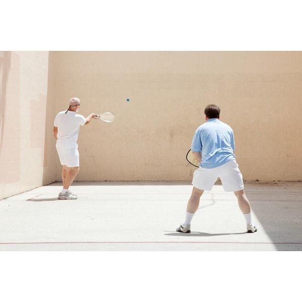 Two men playing racquetball on an outdoor court.
