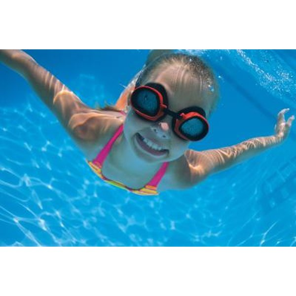 Young girl wearing goggles under water.