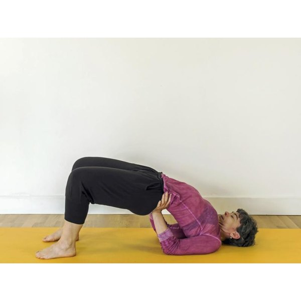 A woman holding bridge pose on a yoga mat.