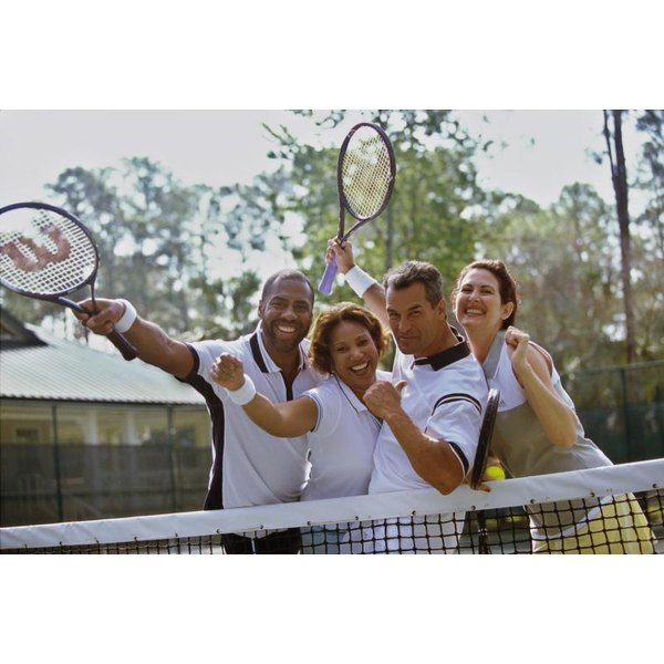 Smiling couples on tennis court holding up rackets.