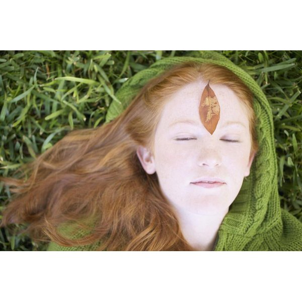A close-up of a woman meditiating in the grass with a leaf over her third eye.
