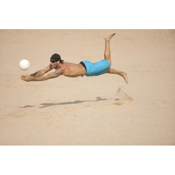 Volleyball player diving for ball on sand.