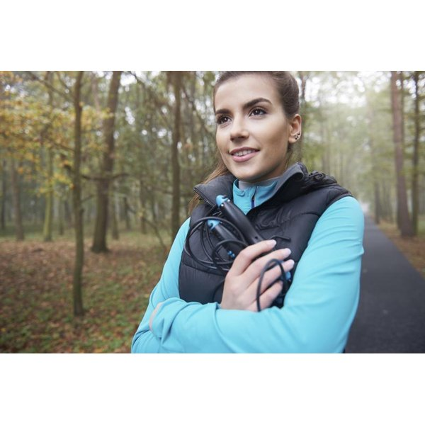 A young woman holding a jump rope on an exercise path in the woods.