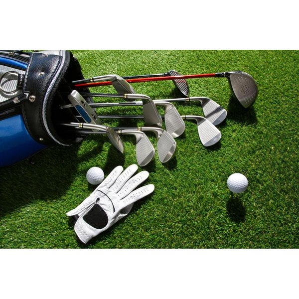 Golf clubs in bag next to balls and glove on grass.