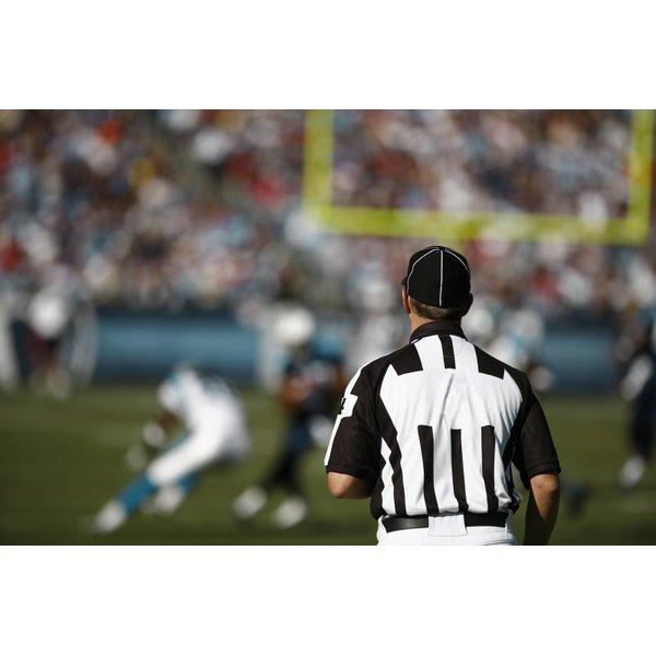 A football official watches a play unfold.
