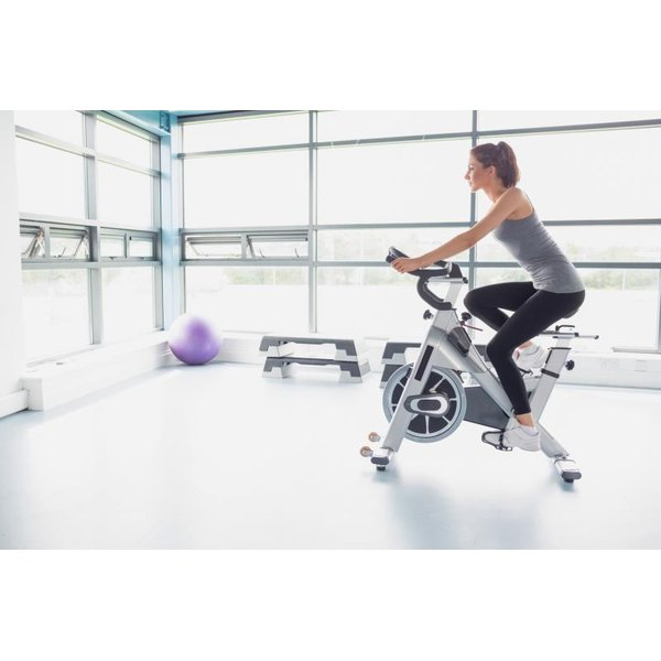 A woman riding a stationary bike in a gym.