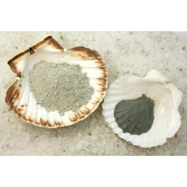 Two shells holding dry and wet clay on a bed of sea salt.