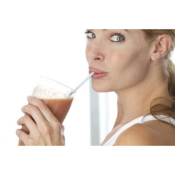 Side view of woman drinking a protein drink through a straw.