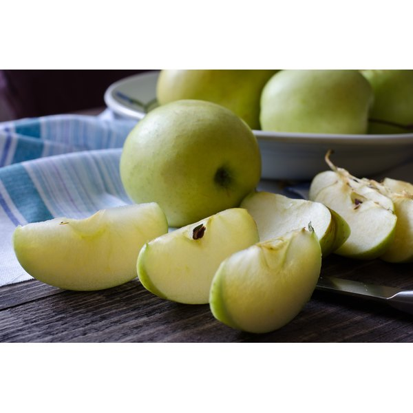 Apple slices on a wooden cutting board.