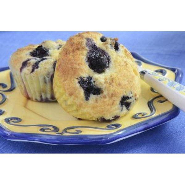 Close up of 2 fresh blueberry muffins on a plate.