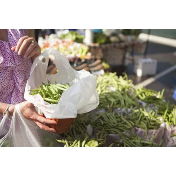 A woman buys green beans at a farmer's market.