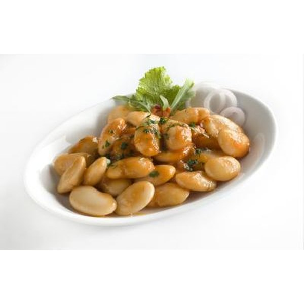 Great Northern beans in a white bowl with garnish.