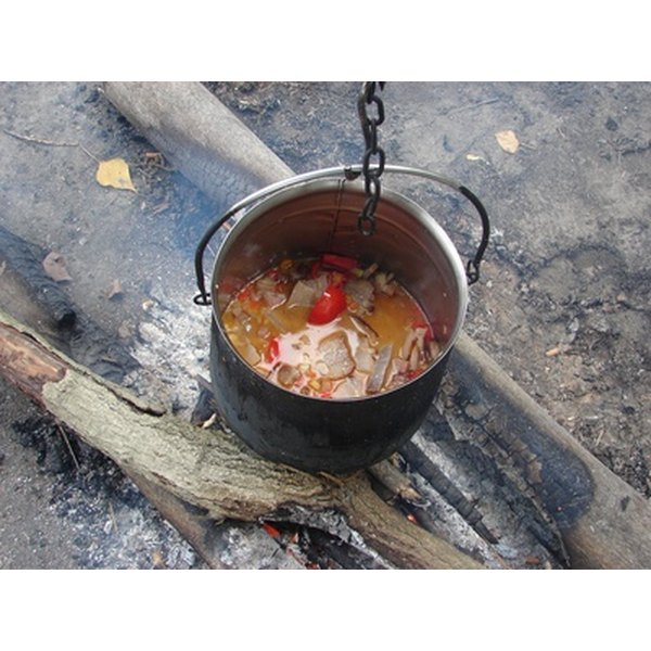 A savory stew cooks in an aluminum Dutch oven .