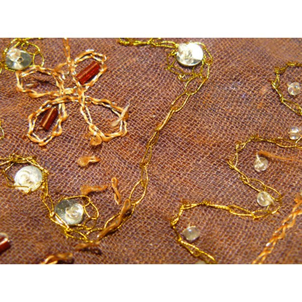A sequin design is sewn onto a piece of fabric.