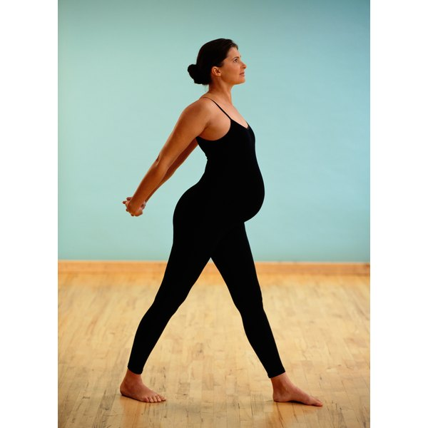 Pregnant woman stretching in studio.
