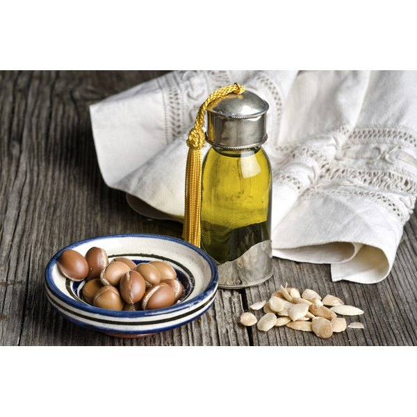 A bottle of argan oil next to argan nuts and a napkin.. .