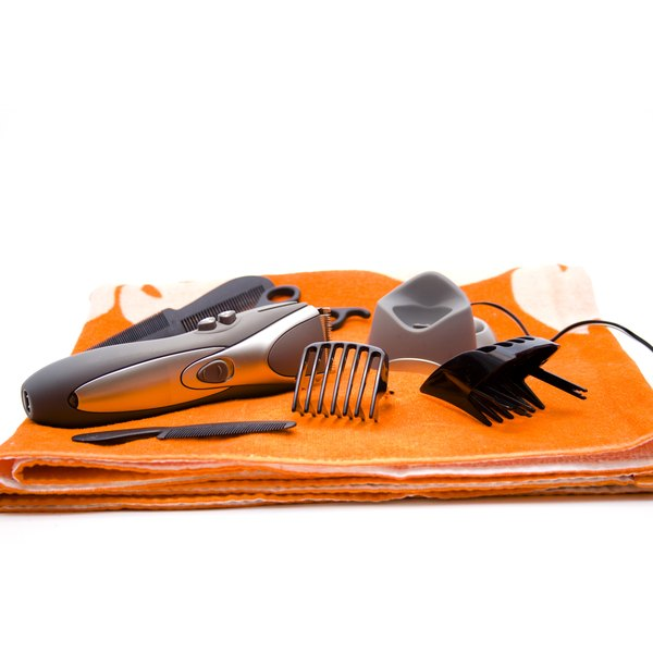 Home hair clippers and all the components sit on an orange towel in the bathroom.