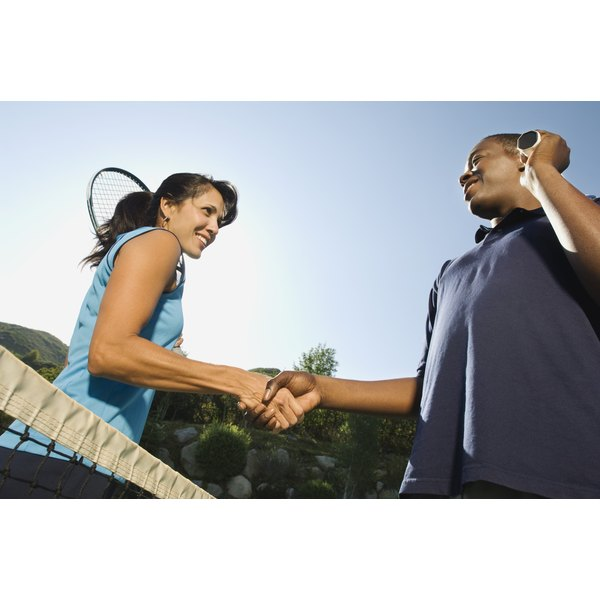 A man and a woman shake hands after a tennis match.