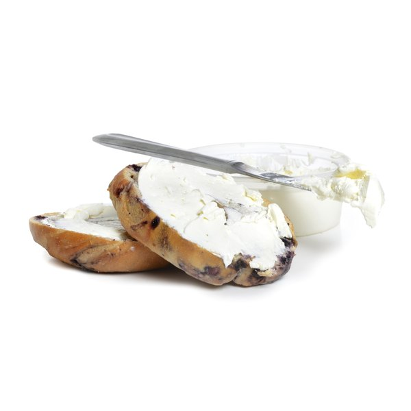 A cinnamon raisin bagel is spread with low-fat cream cheese.
