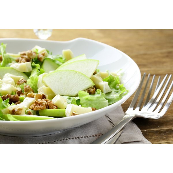 Salad with apples and nuts on a white plate.
