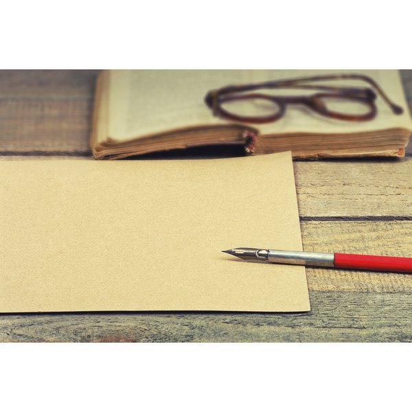 An old poetry book, glasses, paper and a calligraphy pen on a table.