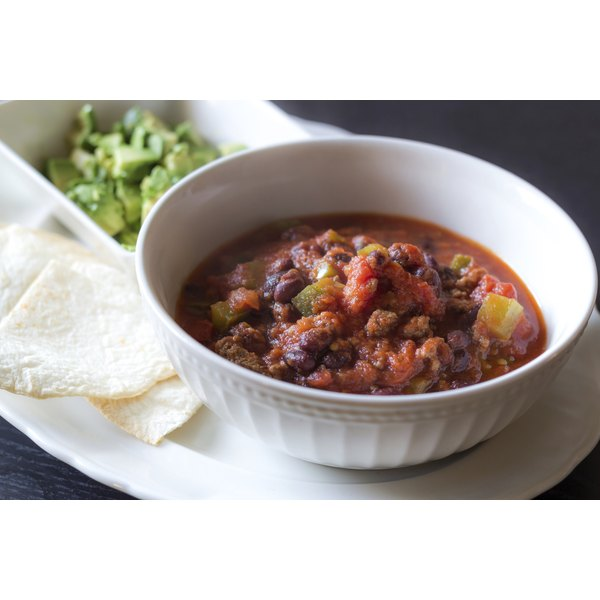 A bowl of spicy chili with tortillas and avocado.
