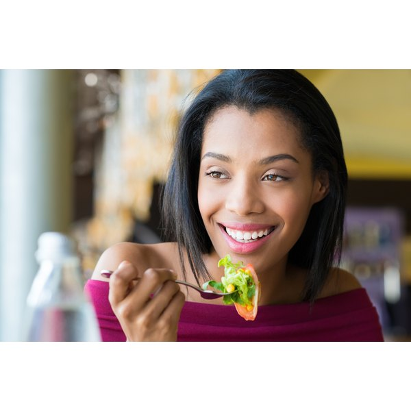 An energetic woman eating a salad.