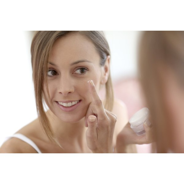 A woman applies anti-aging cream in the mirror.