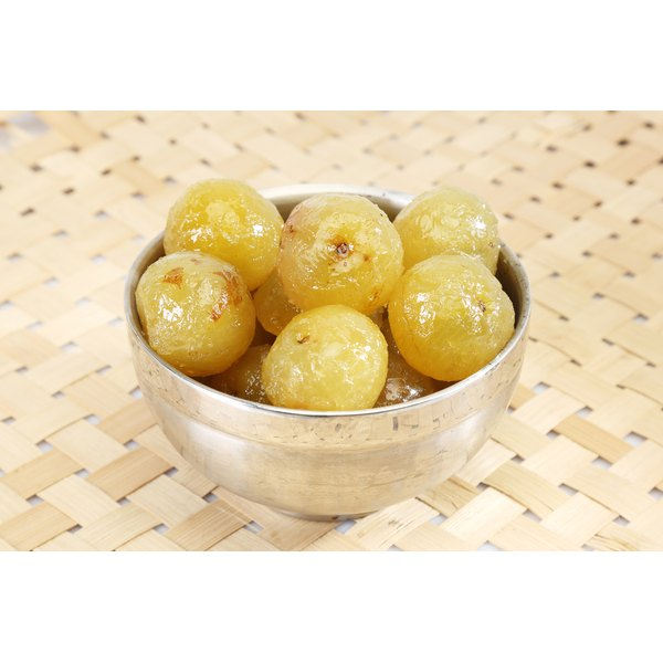 Sweetened amla in a bowl on a straw mat.