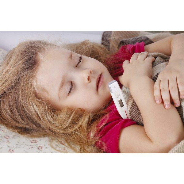 A little girl resting in bed with a thermometer underneath her arm.