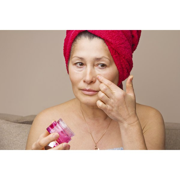 Middle-aged woman with towel on her hair putting on face cream