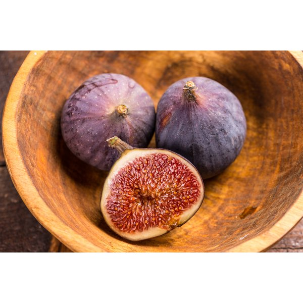 A bowl of fresh figs on a table.