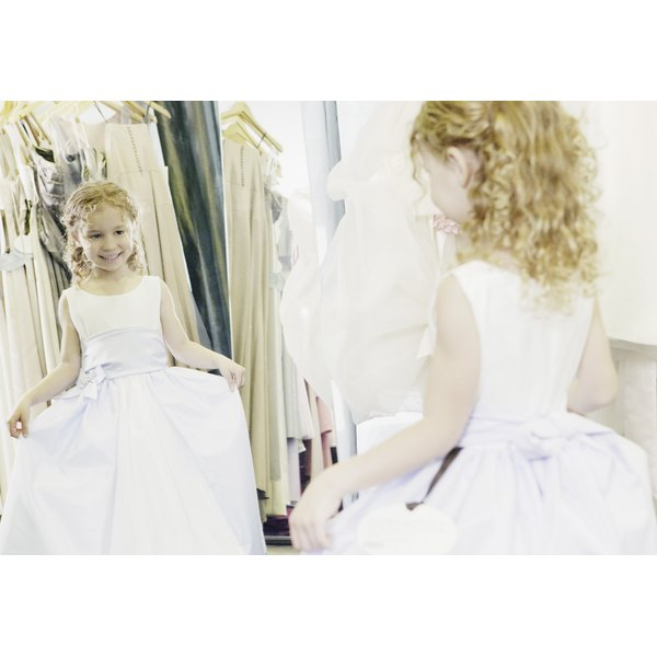 A flower girl's dress is made sweeter with a silk ribbon tied around the waist.