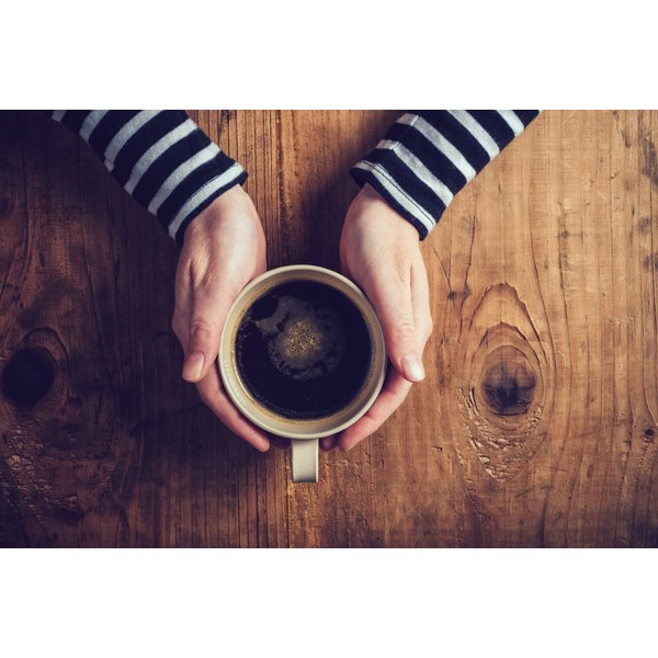 A woman's hands holding a cup of coffee.