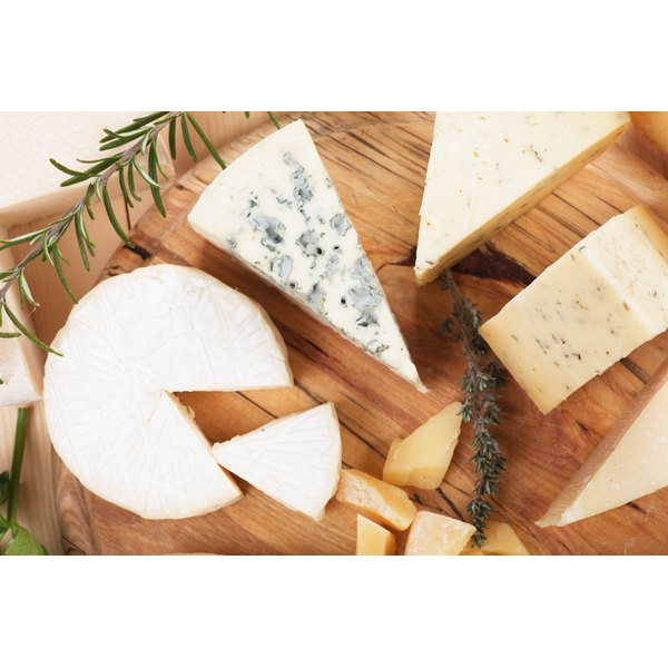 A selection of cheeses on a wooden cutting board.