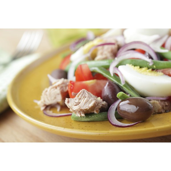 A salad with flaked tuna, egg, olives, tomatoes, red onions and green beans.
