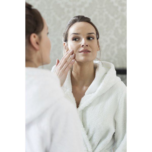 Woman looking at her face in the mirror.