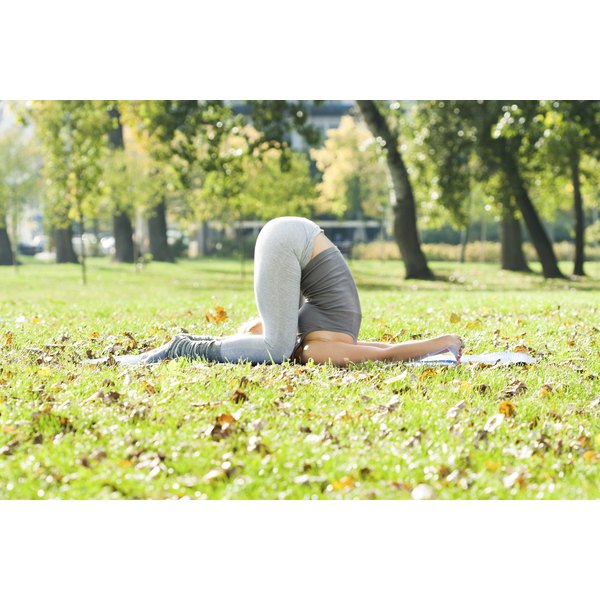 A woman assumes the karnapidasana pose while in a park.